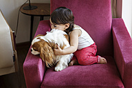 Toddler girl sitting on an armchair cuddling with dog - LITF00572