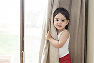 Portrait of a toddler girl playing peek-a-boo behind the curtain - LITF00575