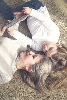 Mother and daughter lying on carpet looking at tablet - RTBF00753