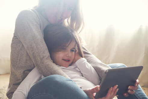 Mother and little daughter using tablet at home - RTBF00759