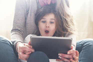 Portrait of astonished little girl using  tablet with her mother - RTBF00762