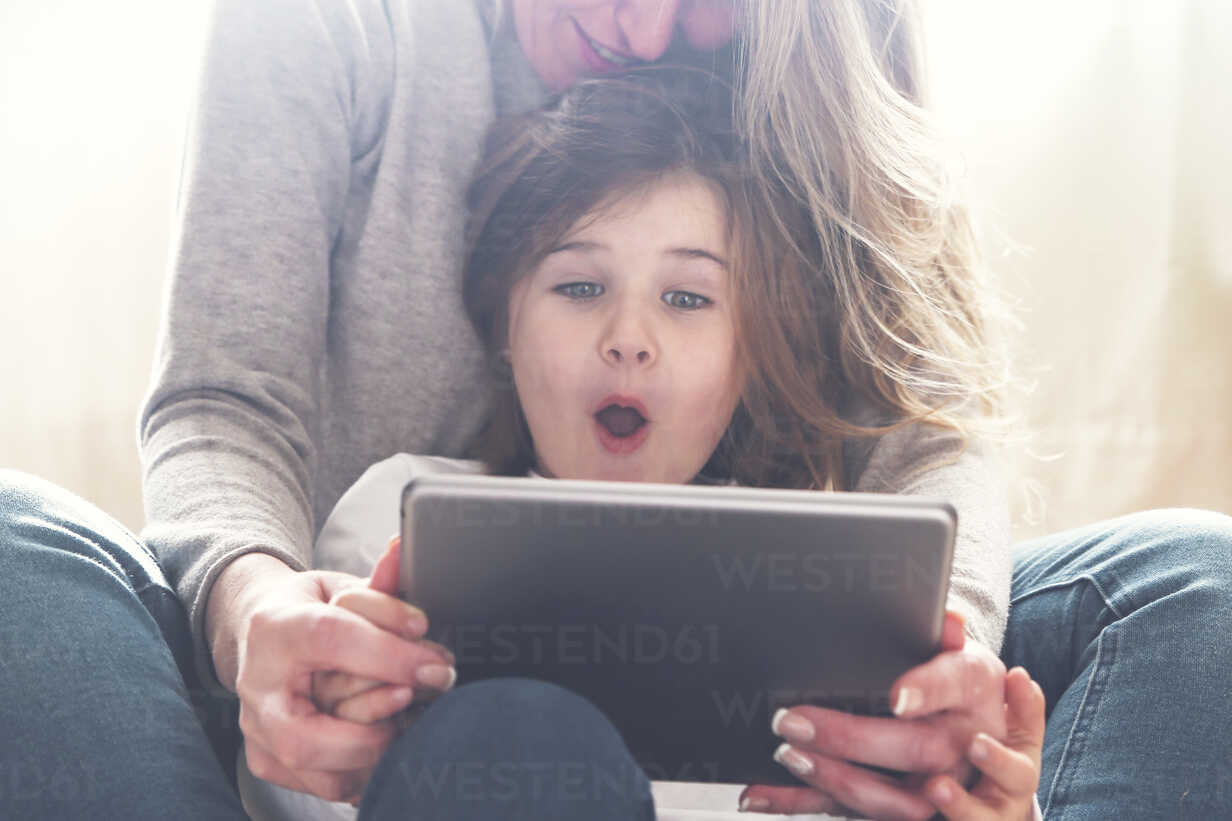 Portrait of astonished little girl using  tablet with her mother - RTBF00762 - Retales Botijero/Westend61