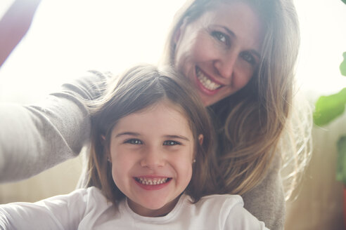 Portrait of mother and little daughter  taking selfie at home - RTBF00765