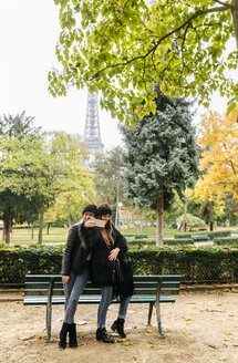 France, Paris, two young women taking a selfie in park with the Eiffel Tower in the background - MGOF03093