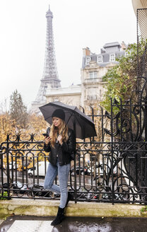 France, Paris, young woman using her smartphone with the Eiffel Tower in the background - MGOF03099