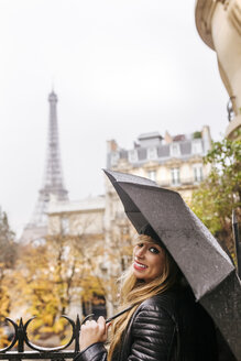 France, Paris, young woman under umbrella with the Eiffel Tower in the background - MGOF03102