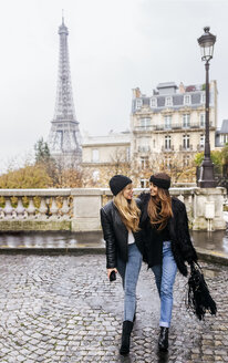 France, Paris, two best friends walking down the street with the Eiffel Tower in the background - MGOF03105