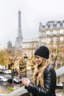 France, Paris, young woman using her smartphone with the Eiffel Tower in the background - MGOF03108