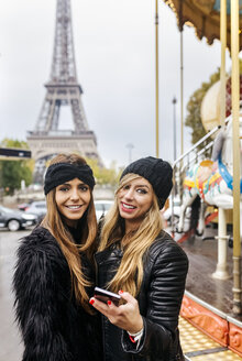 France, Paris, two best friends with a carousel and the Eiffel Tower in the background - MGOF03111