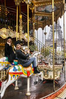 France, Paris, two best friends riding a carousel with the Eiffel Tower in the background - MGOF03114
