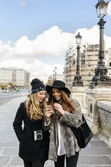 France, Paris, two female tourists walking in the city looking at cell phone - MGOF03117