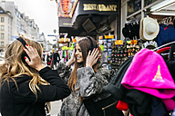 France, Paris, two female tourists at a souvenir stand - MGOF03120