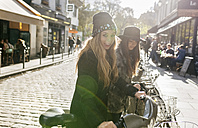 France, Paris, two female tourists using rental bikes - MGOF03126
