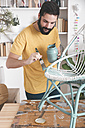 Bearded man painting wicker armchair at home - RTBF00768