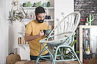 Bearded man painting wicker armchair at home - RTBF00771