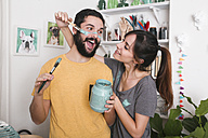 Young woman painting her boyfriend's face with paintbrush - RTBF00780