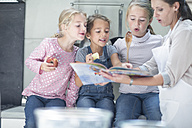 Mother and three girls in kitchen looking in book - ZEF13223