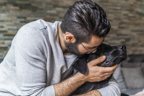Man cuddling with his dog at home - TCF05319