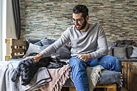 Man stroking his dog on the couch at home - TCF05322