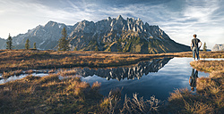 Austria, Hochkoenig, Mandlwand and man standing at moor pond - STCF00294