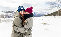 Two young women hugging in the snow - MGOF03127