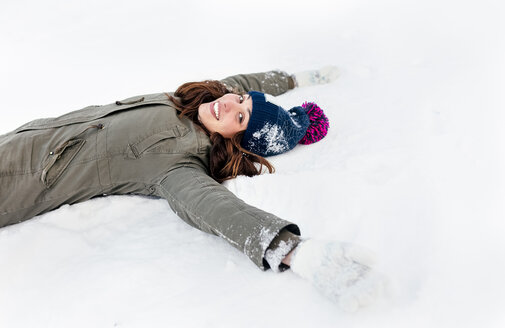 Smiling young woman lying the snow - MGOF03136