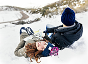 Young couple lying in the snow - MGOF03145