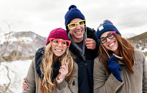 Three friends with fake glasses having fun in the snowy mountains - MGOF03154