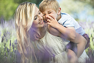 Happy mother with son in lavender field - ZEF13233
