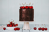 Cake with chocolate icing and cherries on cake stand - RTBF00786