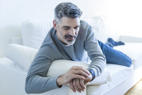 Mature man at home lying on couch and checking the time - TCF05342