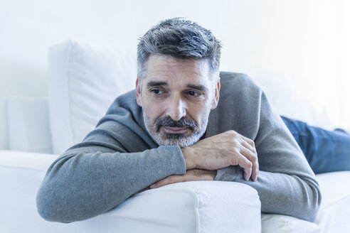 Relaxed mature man at home lying on couch - TCF05345