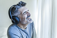 Emotional mature man with closed eyes wearing headphones - TCF05348
