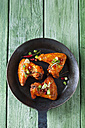 Three marinated and grilled chicken wings in cast-iron frying pan - CSF28208