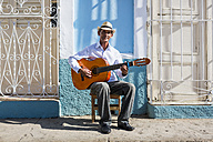 Cuba, Trinidad, portrait of man  playing guitar on the street - MAUF01022