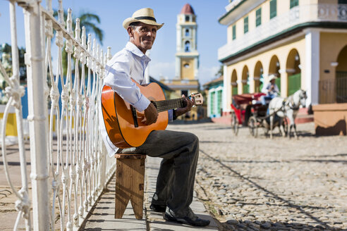 Cuba, Trinidad, man playing guitar on the street - MAUF01025