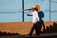 Cuba, man with guitar walking on the street - MAUF01037