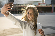 Portrait of young woman taking selfie with smartphone - KKAF00548