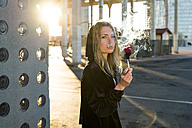Portrait of blond young woman smoking cigarette - KKAF00551