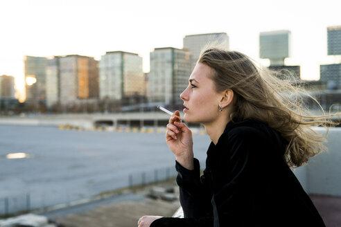 Spain, Barcelona, pensive young woman smoking cigarette - KKAF00566