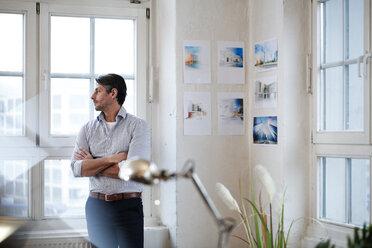 Man in office looking out of window - FKF02198