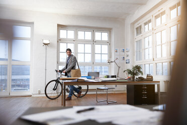 Man with bicycle in a modern informal office - FKF02201