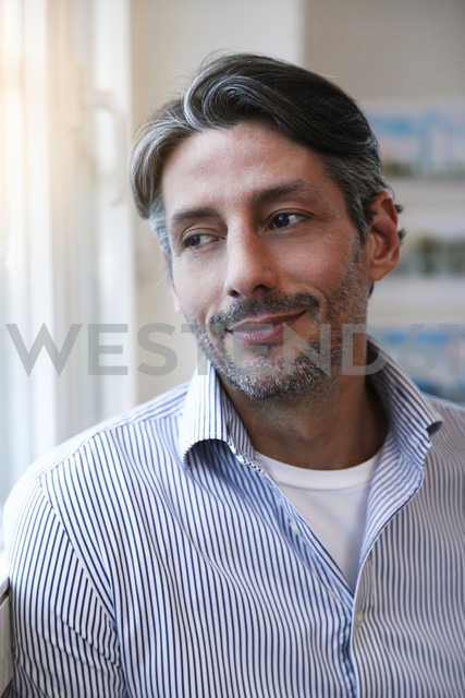 Smiling man in office looking out of window - FKF02207