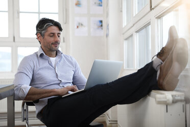 Man using laptop at the window in office - FKF02210