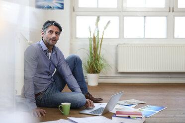 Man using laptop on the floor in office - FKF02213