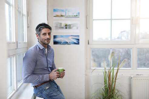 Portrait of smiling man with cup of coffee in office - FKF02216