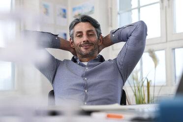 Portrait of smiling man at desk in office - FKF02219