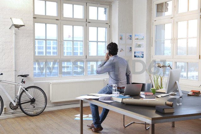 Man using cell phone in a modern informal office - FKF02225