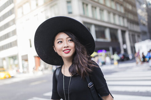 USA, New York City, Manhattan, portrait of fashionable young woman wearing black hat - GIOF02480