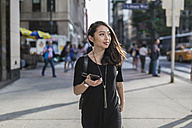 USA, New York City, Manhattan, portrait of young woman with cell phone dressed in black - GIOF02483